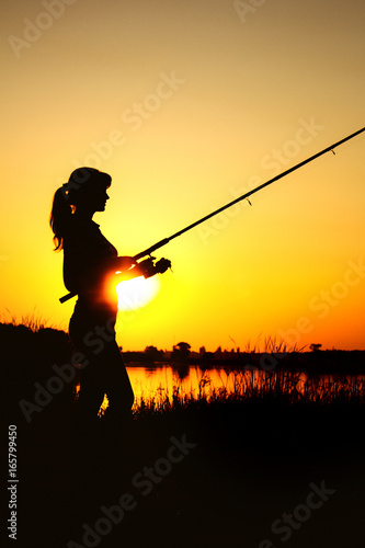 Fotobehang Jacht Silhouette of a woman with a fishing rod on nature