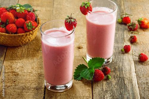 Fotobehang Milkshake Fresh strawberry milkshake on a wooden table. Healthy fruit smoothie drink.