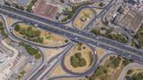 Vista aerea di un uscita autostradale a roma. Le auto corrono veloci lungo l'autostrada mentra alcune si stanno immettendo o ne sta uscendo tramite la corsia di accellerazione o decellerazione.
