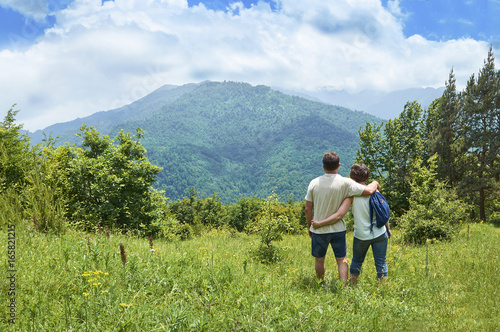 Middle-aged couple of tourists standing embraced and enjoying beautiful mountain Poster