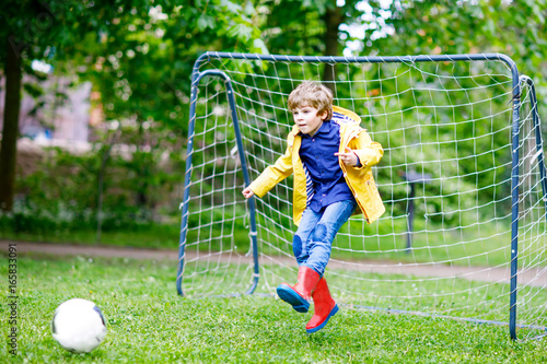 Active cute little kid boy playing soccer and football and having fun