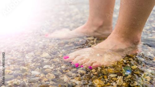 Schöne Füße mit violetten Fußnägeln im flachen Wasser