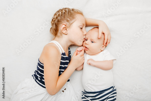 Lifestyle portrait of cute white Caucasian girl sister holding kissing little baby, lying on bed indoors. Older sibling with younger brother newborn. Family love bonding together concept.