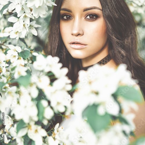 Beautiful young woman surrounded by flowers of apple-tree - 165834439