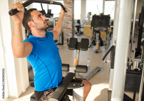 Poster Fit man exercising at the gym on a machine