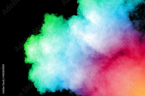 Abstract art colored powder on black background. Frozen abstract movement of dust explosion multiple colors on black background. Stop the movement of multicolored powder on dark background. - 165845801