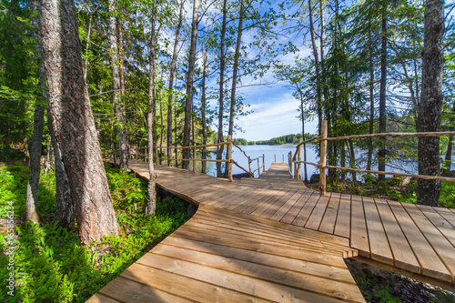 Tuinposter Grijze traf. Wooden paths along the lake in the spring forest of Karelia
