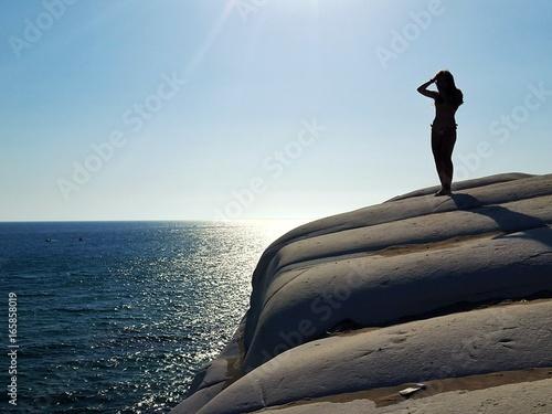 Estate al mare con ragazza sugli scogli