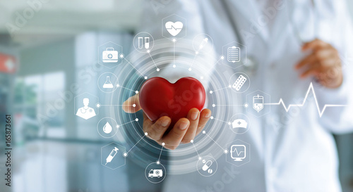 Medicine doctor holding red heart shape in hand and icons medical network connection with modern virtual screen interface, medical technology network concept © ipopba