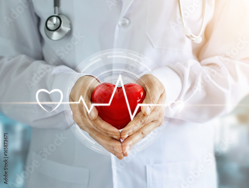 Doctor with stethoscope and red heart shape with icon heartbeat in hands on hospital background © ipopba
