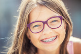 Fototapety Happy smiling girl with dental braces and glasses. Young cute caucasian blond girl wearing teeth braces and glasses