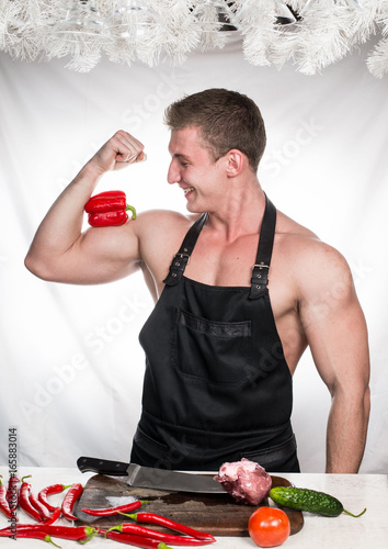 Chef bodybuilder laughs preparing a dinner of vegetables and meat