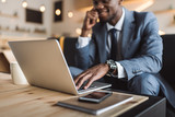 selective focus of handsome african american businessman using laptop in cafe