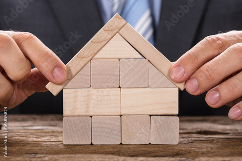 Businessman Making Model House With Wooden Blocks - 165895824