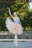 Young beautiful ballerina dancing outdoors in a park. Full length portrait. - 165909811