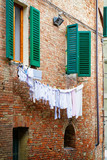 Traditional house with hanging clothes on clothesline in Siena