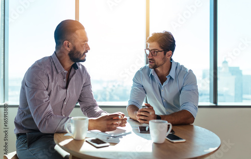 Business partners discussing business plans sitting at table in - 165913880