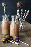 Bottles of chocolate milk with straws and cake pops