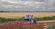 A farmer uses a disc harrow to roll corn stubble back into the soil for nutrients for next season.