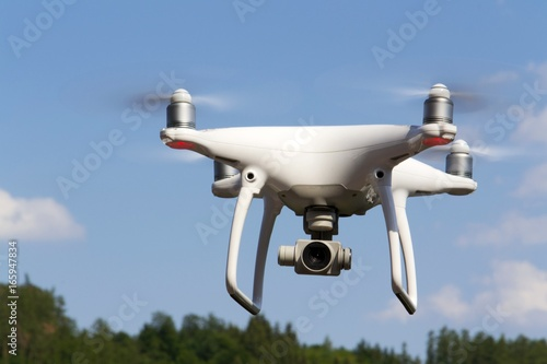 Juliste White drone quadrocopter with camera flying over forest