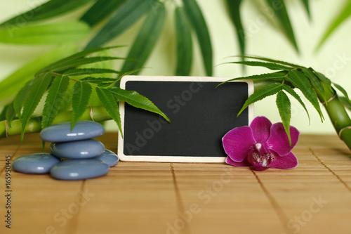 Galets gris disposés en mode de vie zen avec une orchidée,une bougie allumée ,un branche de bambou et des feuillages et une ardoise à message vide