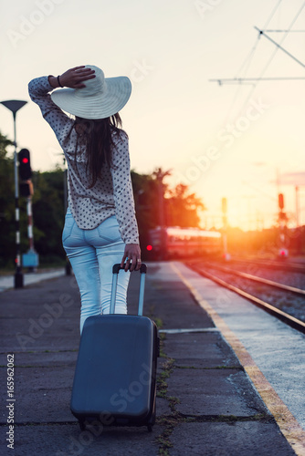 Woman traveler with luggage near railroad tracks in sunset. Back view.