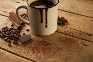 Vintage mug of hot chocolate drink with cinnamon sticks coffee beans anise and piece of chocolate on old wooden rustic table with copy space.