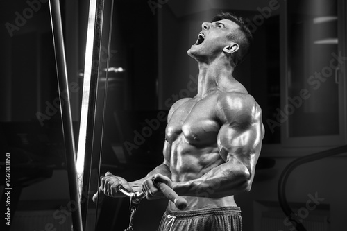 Poster Muscular man working out in gym doing exercise, strong male torso abs