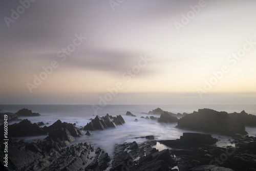 Beautiful long exposure landscape image of sea over rocks during vibrant sunset