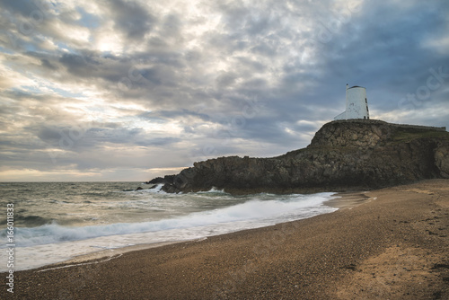 Stunning Twr Mawr lighthouse landscape from beach with dramatic sky and cloud fo Poster