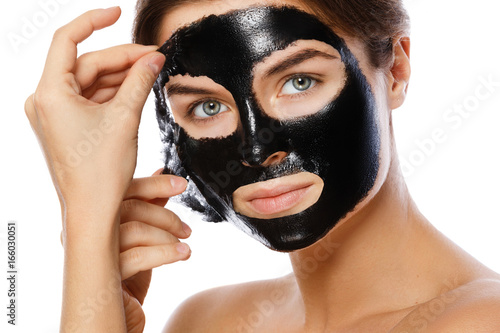 Beautiful woman is removing purifying mask from her face