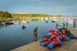 Lobster buoys in a large pile on the dock overlook the harbor