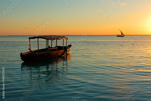 Poster Zanzibar Wooden boat on water at sunset, Zanzibar island.
