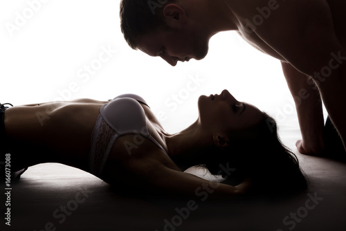Thin gorgeous woman lays on the floor and handsome man wants to kiss her