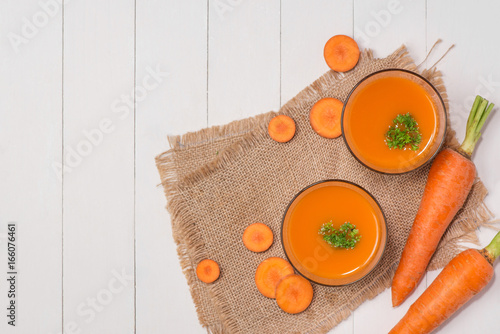 Poster Sap Fresh carrot juice in glass on wooden table.