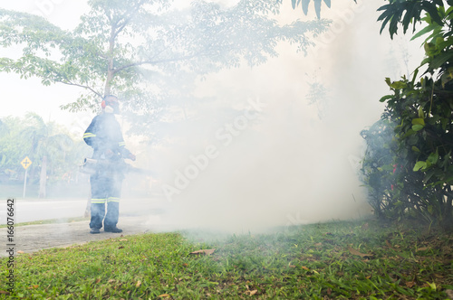 PUTRAJAYA, MALAYSIA - JULY 29, 2017 : Unidentified pest control operator from Ministry Of Helath Malaysia fogging to eliminate mosquito for preventing spread dengue fever and zika virus. - 166076642