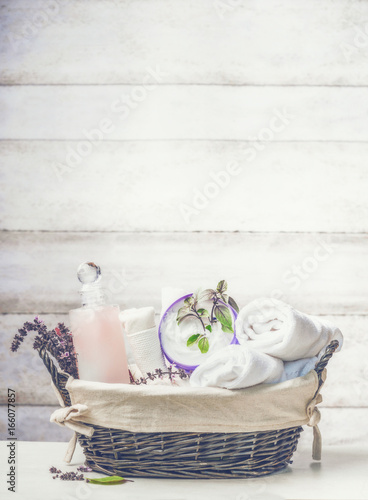 canvas print picture Basket with spa ,wellness or beauty setting on white wooden background, front view
