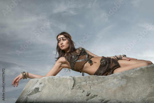 Young beautiful woman dressed in a leather wear looking like an amazon or warrior lying on a big stone Poster