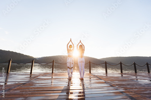 Two young women doing yoga at nature. Fitness, sport, yoga and healthy lifestyle concept - group of people making yoga pose on lake pier