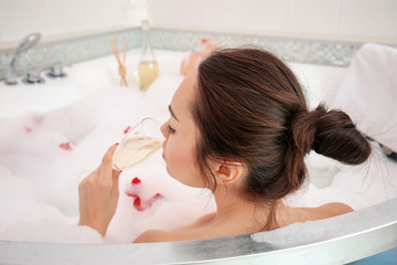 Beautiful woman with glass of champagne in bathtub © Africa Studio