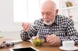 Senior man eating fresh salad copy space
