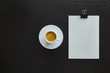 notepad and espresso on dark wooden table