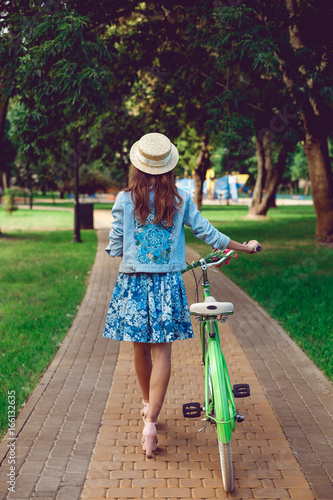 View from the back of a beautiful woman goes with a retro bicycle. Girl in dress and straw hat. Active lifestyle in the park.