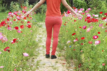 A happy girl in red walks along a path from red poppies, summer time