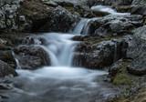 Small waterfall on mountain river Zagedanka. Landscape in gray tone. Caucasus mountains.