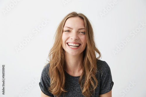 Young cheerful happy girl smiling laughing looking at camera over white background.
