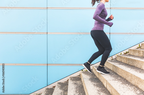Woman jogging and running up a staircase