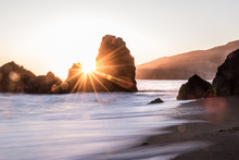 Sunburst between rocks on the beach in the Golden Gate of California