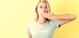 Young woman covering her mouth on a yellow background