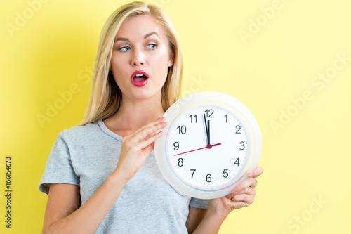 Fotobehang Muziek Young woman holding a clock showing nearly 12